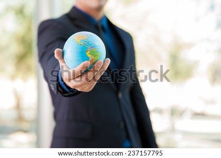 Closeup of a businessman holding a small globe in his hand - stock photo