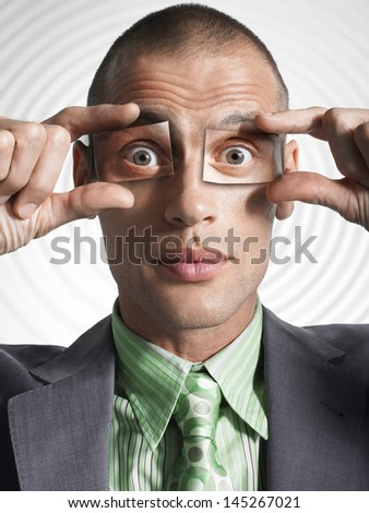Closeup of a businessman holding photos of eyes in front of his own eyes - stock photo