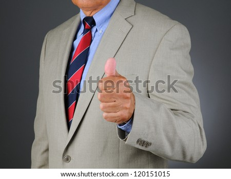 Closeup of a businessman in a light-colored suit giving the thumbs up gesture. Horizontal format showing only the mans torso. Light ot dark gray background. - stock photo