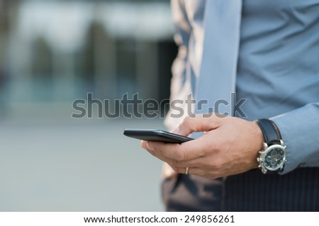Closeup Of A Businessman's Hand Holding Cellphone - stock photo