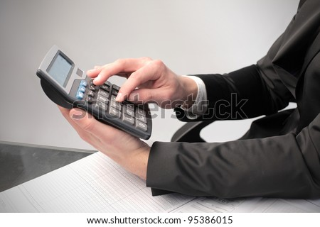 Closeup of a businessman's hands using a calculator
