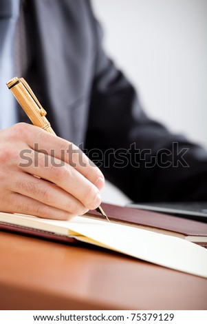 Closeup of a businessman's hands while writing some documents - stock photo