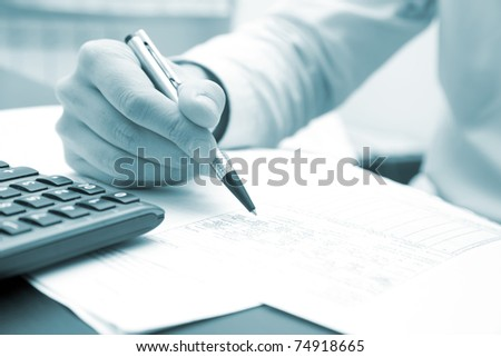 Closeup of a businessman's hands while writing some documents - blue toned image - stock photo