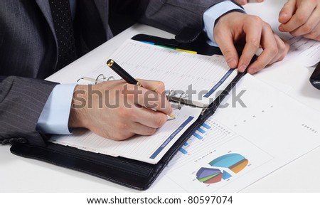 Closeup of a businessman seated at his desk and writing in notebook