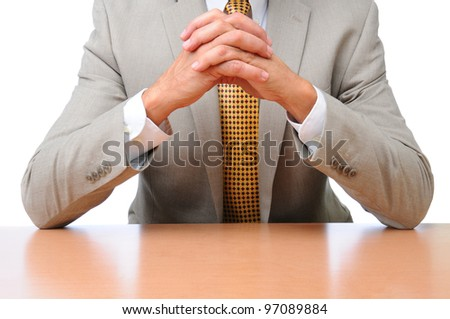 Closeup of a businessman seated with his elbows on his desk with hands clasped together. Horizontal format over white, man is unrecognizable. - stock photo