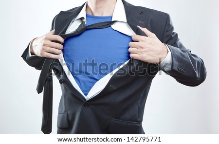 Closeup of a businessman showing the superhero suit under his shirt - stock photo
