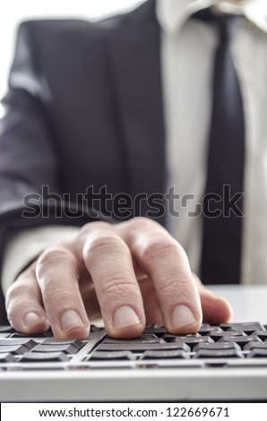 Closeup of a businessman using computer. His suit and tie in background. - stock photo