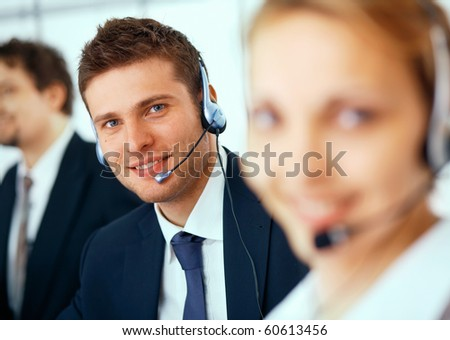 Closeup of a businessman with headset, her colleagues at the background and foreground - stock photo