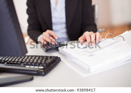 Closeup of a businesswoman doing finances in the office - stock photo