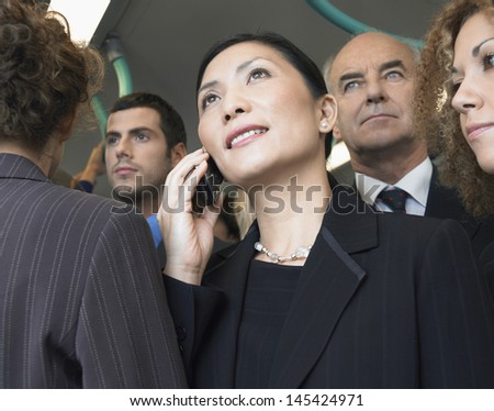 Closeup of a businesswoman using mobile phone in train amid commuters - stock photo