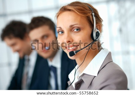 Closeup of a businesswoman with headset, her colleagues at the background.