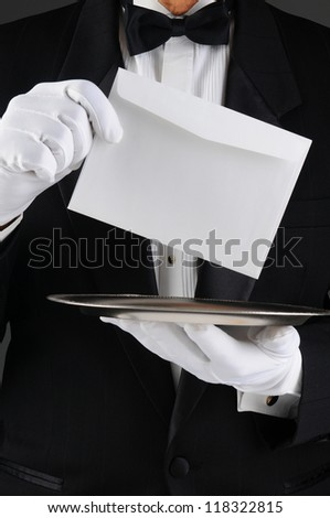 Closeup of a butler wearing a tuxedo holding a silver tray and an envelope. Vertical format, man is unrecognizable. - stock photo