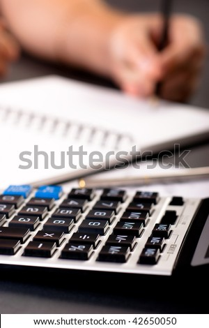 Closeup of a calculator in office environment - stock photo