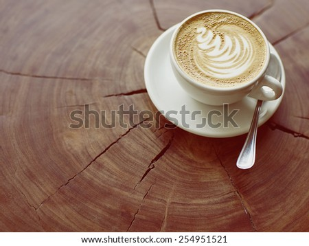 Closeup of a cappucino on a wooden stump with beautiful natural patterns - stock photo