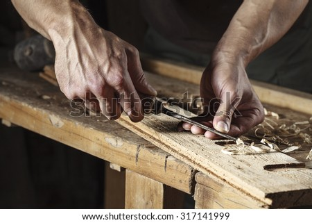 Closeup of a carpenter hands working with a chisel and carving tools on wooden workbench - stock photo