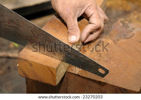 Closeup of a carpenter sawing a piece of wood.