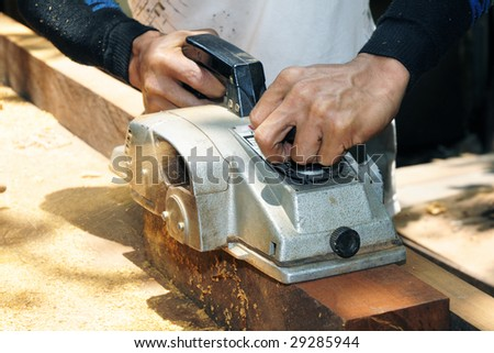 Closeup of a carpenter working with a power belt wood sander. - stock photo