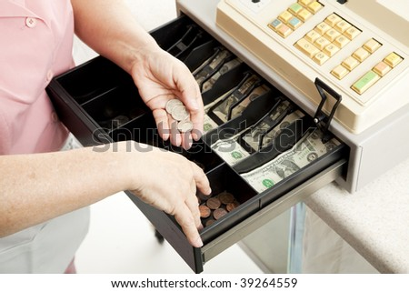Closeup of a cashier's hands making change from a full cash register. - stock photo