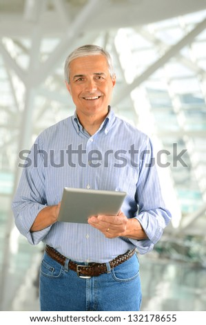 Closeup of a casual businessman in a modern factory holding a tablet computer. Vertical Format. - stock photo
