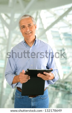 Closeup of a casual businessman in a modern factory setting holding a tablet computer. Vertical Format. - stock photo