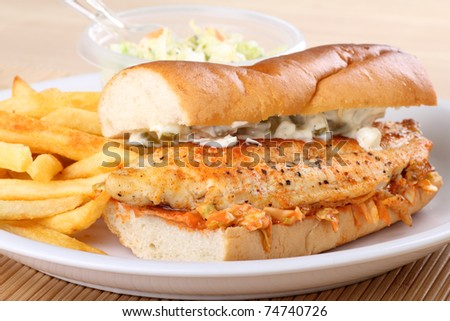 Closeup of a catfish fillet sandwich with french fries and coleslaw - stock photo