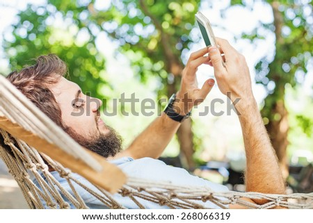 closeup of a caucasian man using mobile phone white swinging in  - stock photo
