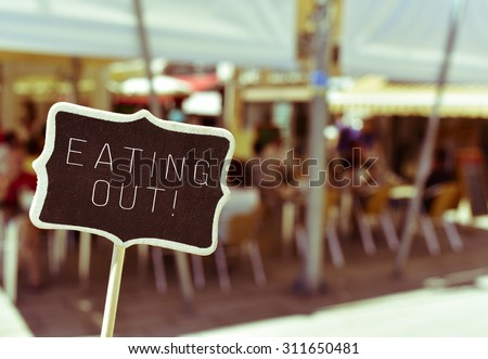 closeup of a chalkboard with the text eating out, in the busy terrace of a restaurant - stock photo
