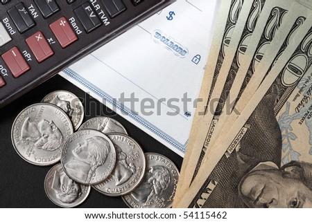 closeup of a checkbook with calculator, coins and twenty dollar bills - stock photo