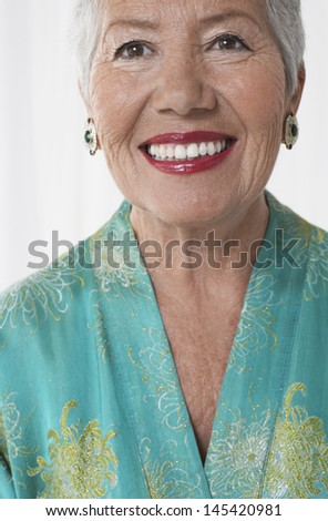 Closeup of a cheerful senior woman in red lipstick against white background - stock photo