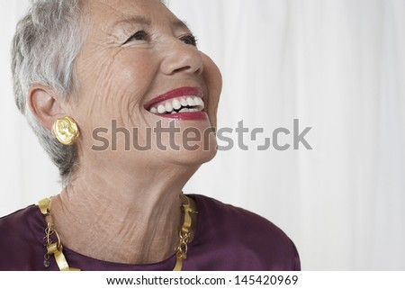 Closeup of a cheerful senior woman looking up against white background - stock photo