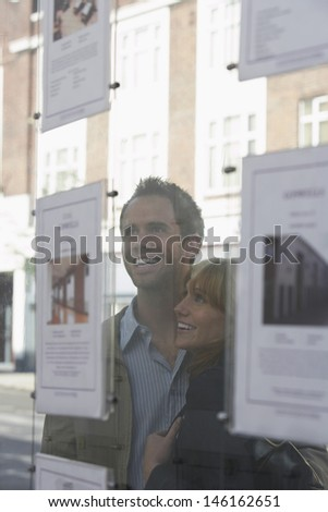 Closeup of a cheerful young couple looking through window at estate agents - stock photo