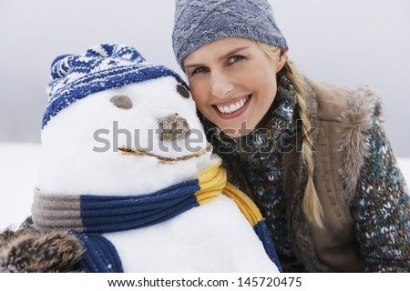 Closeup of a cheerful young woman by snowman on snow covered hill - stock photo