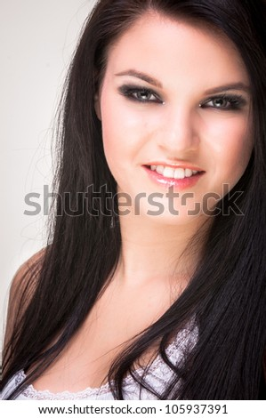 Closeup of a cheerful young woman smiling on white background