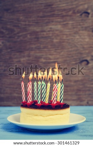 closeup of a cheesecake with some lighted birthday candles of different colors, with a retro effect - stock photo