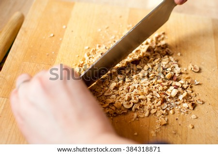 Closeup of a chef chopping nuts with a knife on wooden table. - stock photo