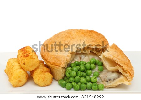 Closeup of a chicken pie with croquette potatoes and peas against a white background - stock photo