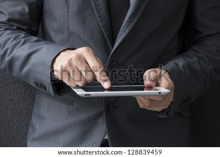 Closeup of a Chinese man with a tablet computer. Asian business man using digital tablet computer, leaning against a black wall. - stock photo