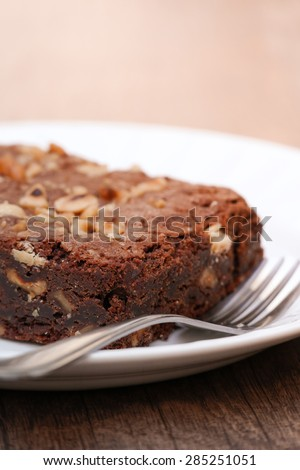 Closeup of a chocolate brownie with hazelnuts on plate with fork - stock photo