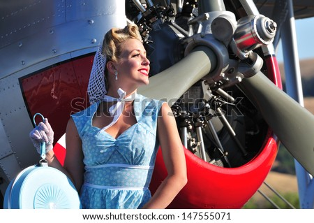 closeup of a classic 1940's lady in front of a vintage biplane - stock photo