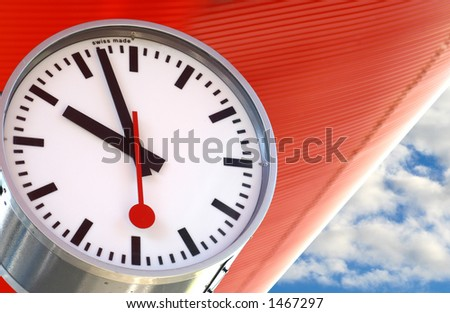 Closeup of a clock against an orange roof and blue sky. - stock photo