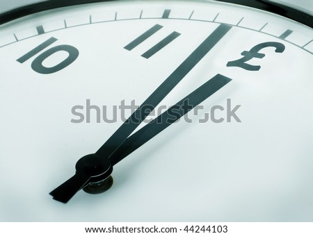 closeup of a clock where the twelve o'clock sign pound symbol - stock photo