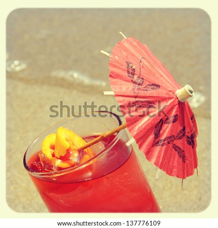 closeup of a cocktail on the sand of a beach, with a retro effect - stock photo