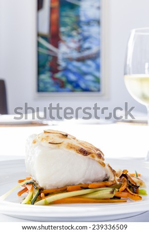 closeup of a codfish loin baked with grilled vegetables served on a plate and a glass of white wine on a restaurant background - stock photo