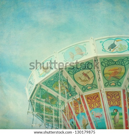 Closeup of a colorful carousel with blue sky background, with vintage style texture editing - stock photo