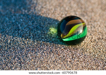 closeup of a colorful marble on sand - stock photo