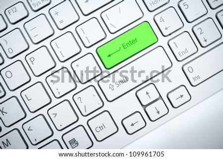 Closeup of a computer keyboard with green button