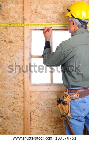 Closeup of a construction worker with a measuring tape marking a point on the wall he is building. - stock photo