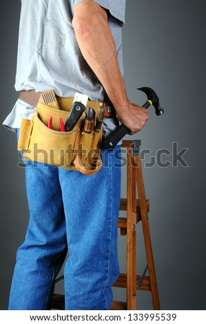 Closeup of a contractor standing on a wooden ladder holding his hammer. Vertical format over a light to dark gray background. Man is unrecognizable.