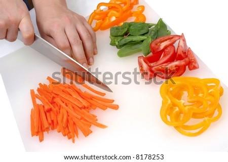 Closeup of a cook's hands chopping fresh veggies - stock photo