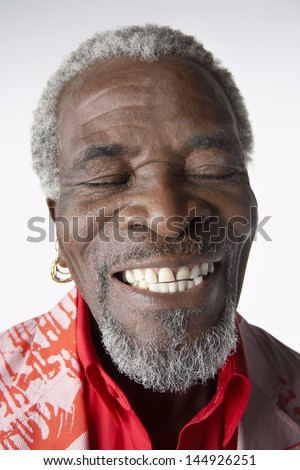 Closeup of a cool smiling senior man with eyes closed against white background - stock photo